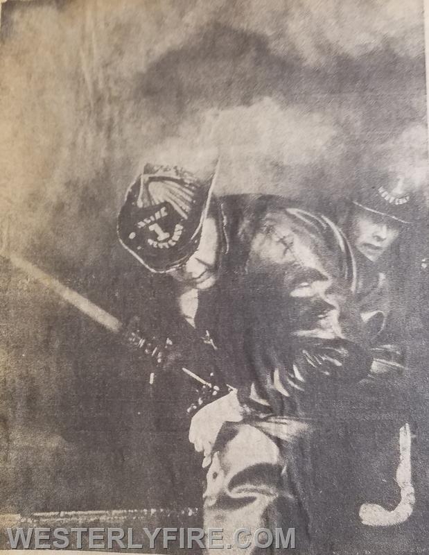 Firefighters Pat Husereau and Larry Rathbun, of  Rhode Island Steam Fire Engine Co. 1 operate a 2 1/2 inside an overhead door in heavy smoke. Box 3152, 2/18/1969