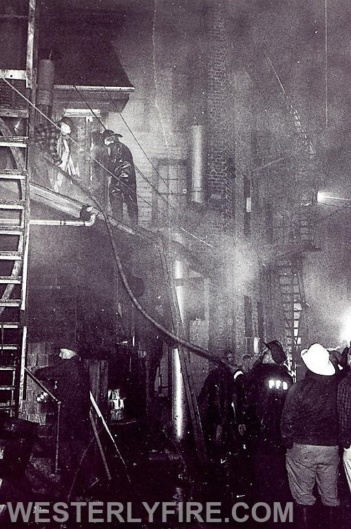 Box 3111-4-23-1964-Westerly and Pawcatuck firefighters advance a hose line over a ladder at the Majestic Hotel on High St.