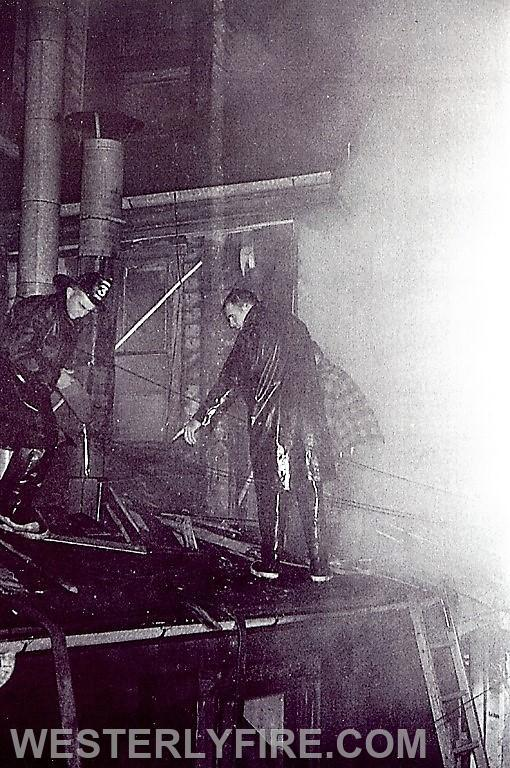 Box 3111-4-23-1964- Members Mario Turco (helmet) and Tom Keena of the Cyclone Engine Co. 2 open up the roof space above the fire at the MajesticHotel.