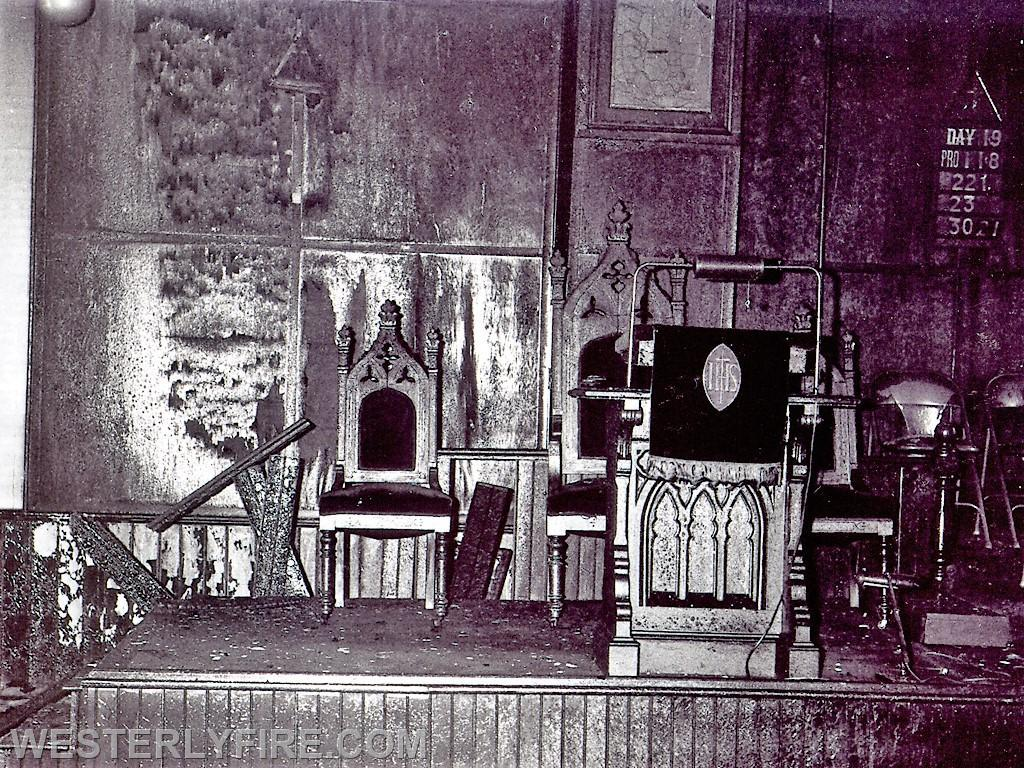 Box 4115 4-23-1964-Heavy charring shows the damage caused to the altar at the Pleasant St. Baptist Church as the fire extended up from the basement.