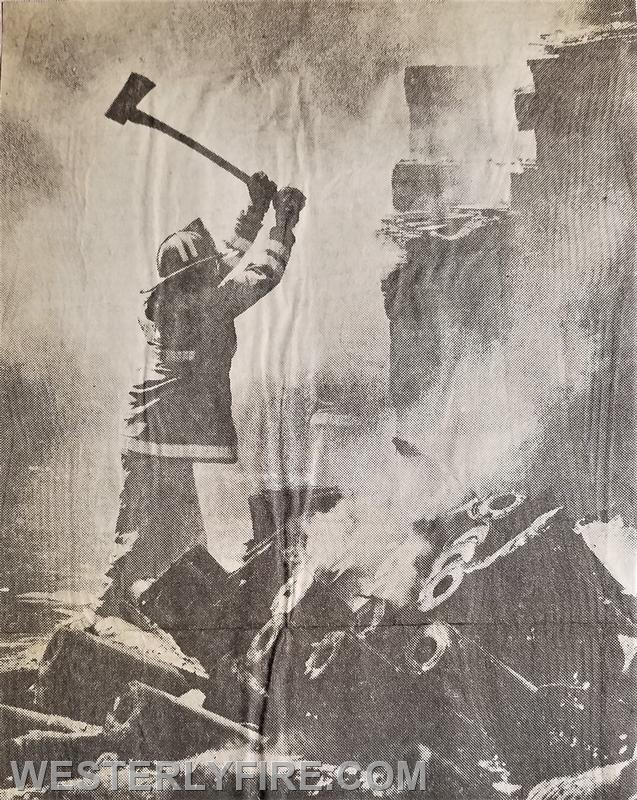Box 3143-7/1/1988-Firefighter Michael Gomes uses an axe to break up roles of tar paper and bundles of wooden shingles to complete overhaul at the UBS fire,