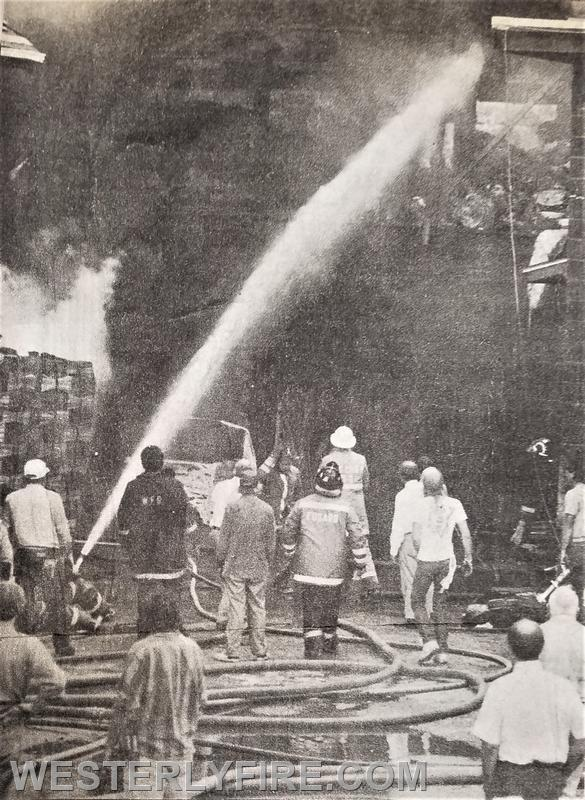 Box 3143-7/1/1988- Westerly and Pawcatuck firefighters spray water into the storage shed at the UBS fire. Fire is visible in the upper right hand corner.
